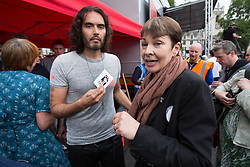 © Licensed to London News Pictures . 20/06/2015 . London , UK . RUSSELL BRAND and CAROLINE LUCAS speaking in Parliament Square . Tens of thousands of people march from the Bank of England to Parliament , to protest economic austerity in Britain . Photo credit: Joel Goodman/LNP