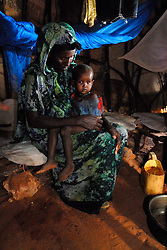 Halima Aden, 37, sits with one of her 7 children Shindia, 2, inside her home that was hit by a flash flood 10 days earlier in the village of Dambas, 80 kilometers outside of Wajir, in northern Kenya May 10, 2006. The number of people who are at risk from the severe drought and now flooding in the Horn of Africa is estimated to be around 15 million of which more than 8 million have been identified as being in need of urgent emergency assistance. Though the rains have come and turned the land green, the problems facing the pastoralists still persist after 3 years of drought that resulted in severe livelihood stress, food insecurity, livestock deaths and high rates of malnutrition. (Ami Vitale)