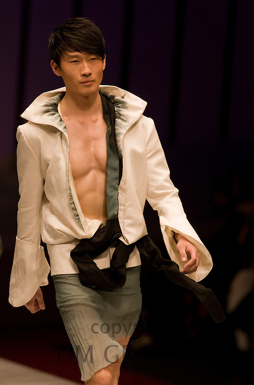 Young man models designer clothes in opening show of China Fashion Week at the Beijing Hotel, China