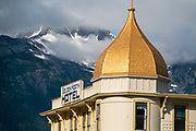 Snow capped peaks rise above Golden North Hotel, Skagway, Alaska, USA. Skagway was founded in 1897 on the Alaska Panhandle. Skagway's population of about 1150 people doubles in the summer tourist season to manage more than one million visitors per year. Half of Alaska's total visitors come via cruise ships. Klondike Gold Rush National Historical Park commemorates the late 1890s Gold Rush with three units in Municipality of Skagway Borough: Historic Skagway; the White Pass Trail; and Dyea Townsite and Chilkoot Trail. (A fourth unit is in Pioneer Square National Historic District in Seattle, Washington.)