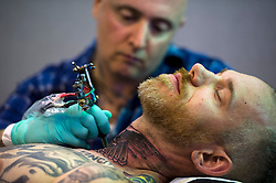 © London News PIctures. 27/09/2013. London, UK. An artist applying a tattoo to a mans neck at The 2013 International London Tattoo Convention held at Tobacco Dock in East London. The event brings over 180 of the world's best tattoo artists to London over three days running from 27th to 29th of September.  Photo credit: Ben Cawthra/LNP