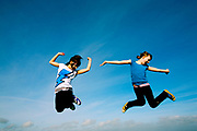 Two young girls leaping into the air enthusiastically<br />  in a field.