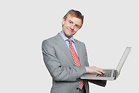 Handsome young businessman using laptop over colored background