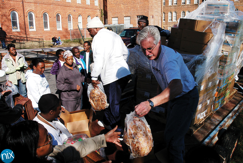 Charles Reed, right, and Sidney Sessons, hand out turkeys  to residents in need as part of New Life Outreach International's Watch Night at Barber-Scotia College in Concord Monday afternoon. Along with the turkeys, volunteers handed out bread, vegetables, fruit, sodas, water and cake to the over 200 residents who showed up. The ministry also held a worship service to ring in the new year Monday night.