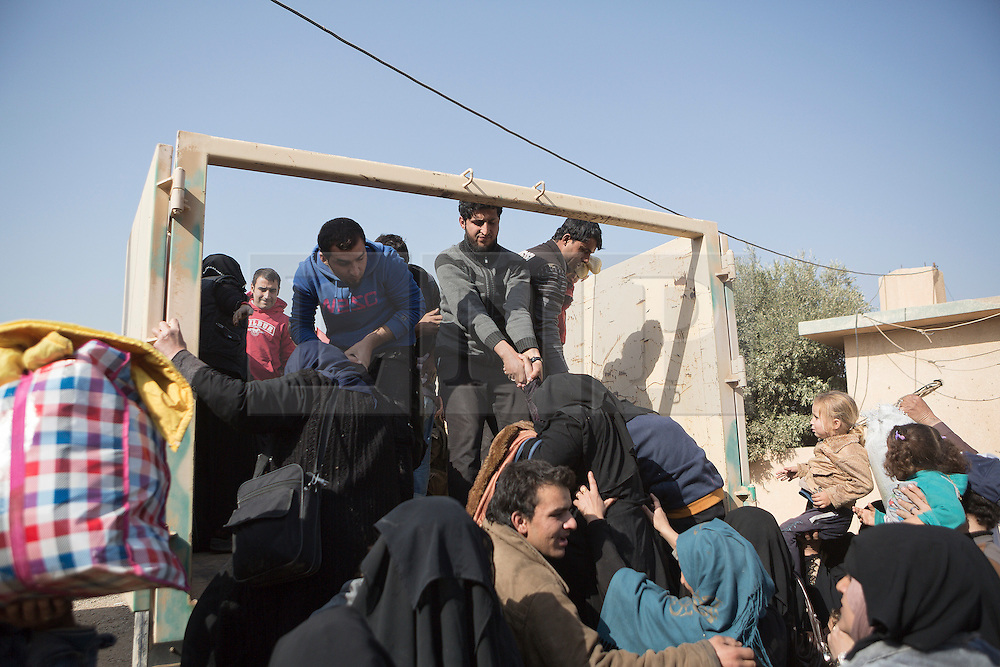 Licensed to London News Pictures. 11/11/2016. Mosul, Iraq. Iraqi refugees, who have fled fighting within Mosul, board Iraqi Army trucks as they prepare to leave the city's Hay Intasar district for the safety of a refugee camp. Hay Intisar district was taken four days ago by Iraqi Security Forces (ISF) and, despite its proximity to ongoing fighting between ISF and ISIS militants, many residents still live in the settlement without regular power and water and with dwindling food supplies.<br /> <br /> The battle to retake Mosul, which fell June 2014, started on the 16th of October 2016 with Iraqi Security Forces eventually reaching the city on the 1st of November. Since then elements of the Iraq Army and Police have succeeded in pushing into the city and retaking several neighbourhoods allowing civilians living there to be evacuated - though many more remain trapped within Mosul.  Photo credit: Matt Cetti-Roberts/LNP