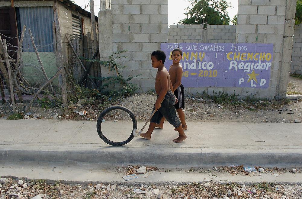 Boys walk down a sidewalk in Sebana Yegua.