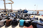 Illegal migrants sit on the dock