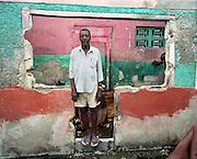 Ces trois photographies sont tire?es d'une se?rie de vingt portraits re?alise?s dans le bidonville de Cite? Soleil adjacent a? la capitale Port-au-Prince. La pauvrete? extre?me engendre la violence et la criminalite? et les habitants en subissent les conse?quences a? tous les jours. Il est impossible pour un e?tranger de pe?ne?trer a? Cite? Soleil sans courrir de graves dangers. Profitant d'un contact exceptionnel aupre?s d'une personnalite? bien connue et respecte?e de cette ville, j'ai pu m'introduirel'espace de quelques heures et re?aliser cette se?rie de photos. Ces diffe?rentes personnes posent devant les ruines de leurs maisons re?cemment de?truites suite aux affrontements d'une extre?me violence de deux bandes criminelles lourdement arme?es se faisant la guerre pour le contro?lede la drogue. J'ai du? faire ces photos rapidement car je sentais la tension monte?e autour de moi, certains e?tant en de?saccord avec ces photos. Ces gens me tiraient par la manche pour que je prenne leur photo dans les ruines de leur maison. Ce fut pour moi un moment d'une grande intensite? e?motive. Toutes les photos ont e?te? re?alise?es avec une came?ra de format 6x7 cm sur du film ne?gatif (Mamiya 7 avec une 65mm)..