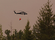 Monday, one of the first two Army National Guard Blackhawk helicopter from the 2-147 that is based in Grand Ledge, MI heads to drop water on a designated target inside the Sleeper Lake forest fire north of Newberry in the upper peninsula.  The fire has been buirning an average of 5,000 acres a day.
