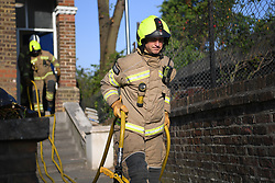 © Licensed to London News Pictures. 16/04/2020. London, UK. Firefighters from Hammersmith Fire Station respond to an early morning call to a bonfire in a garden in west London. As the Lockdown continues LFB (London Fire Brigade) are involved in a rise of domestic call outs as residents stay at home, ranging from BBQs to rubbish burning. Fires outside properties, in gardens and in streets are increasing as are reports of fly-tipping, dumping and waste disposal while local authorities close recycling centres amid the Covid-19 crisis. Photo credit: Guilhem Baker/LNP