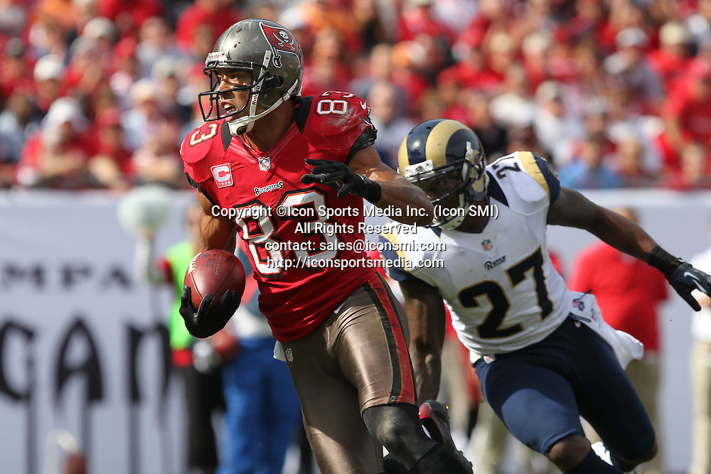 23 December 2012: Buccaneers wide receiver Vincent Jackson (83) tries to avoid being tackled by Rams safety Quintin Mikell (27) after catching a pass during the NFL regular season game between the St. Louis Rams and Tampa Bay Buccaneers at Raymond James Stadium in Tampa, Florida.