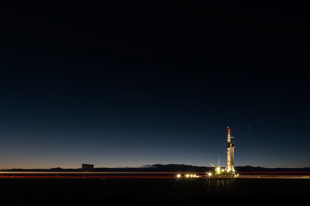 Oil &amp; gas fields of Colorado.In Colorado, drilling happens in plain sight and, in this case, along Interstate I-25, across from the Weatherford facility in Mead, Colorado. This rig has been set up for approx. 3 weeks. My experience is that the wells are horizontal, to approx. 7,000 ft bgs (or deeper), between 4 to 7 wells, in the Niobrara - DJ Basin.<br /> <br /> I was out at sunset scoping out an old abandoned industrial facility in Longmont for a potential photoshoot, but the lighting was a bit screwed up. So, I took a drive to the rig to see what I can see and saw this. This image was taken on pure spec, and portfolio purposes. Anyways, the image was taken using a Nikon D810, Nikon 24-70 lens, tripod, and with a 10 second exposure to capture rush hour traffic along the Cheyenne, WY to Denver, CO corridor. The colored streaks are the truck &amp; car lights. The background features are clouds shrouding the Rockies as a new storm rolls in, with Steamboat expecting up to 10 inches of snow.