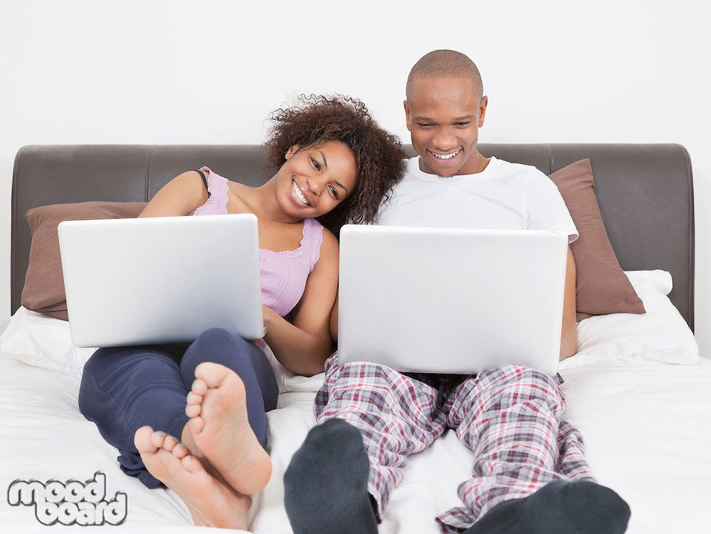 Happy young African American couple using laptops on bed