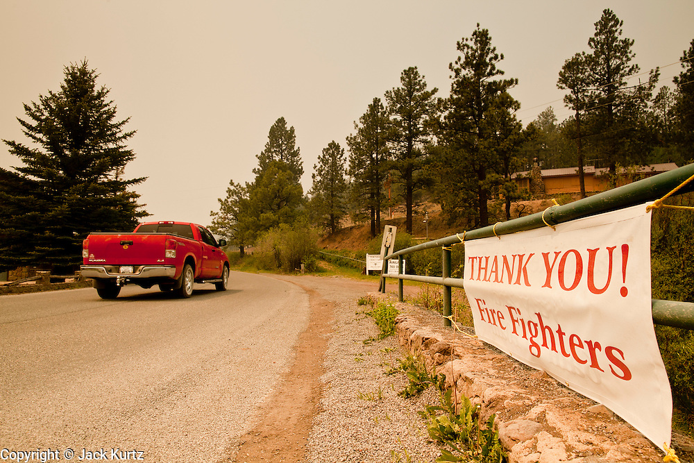 """05 JUNE 2011 - GREER, AZ:  A truck drives into Greer past a sign thanking firefighters Sunday. The fire grew to more than 180,000 acres by Sunday with zero containment. A """"Type I"""" incident command team has taken command of the fire.    PHOTO BY JACK KURTZ"""