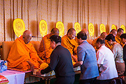 "22 JULY 2014 - BANGKOK, THAILAND:  Members of the Thai elite make merit by giving alms to Buddhist monks during a chanting service and merit making ceremony at Sanam Luang. Hundreds of Thai military officers and civil servants attended a Buddhist chanting service and merit making ceremony to mark the 2nd month anniversary of the May 22 coup that deposed the elected civilian government and ended nearly six months of sometimes violent anti-government protests. The ruling junta said the ceremonies Tuesday were the kickoff to a ""Festival to Bring Back Happiness of the People of the Nation."" There will be free concerts, historical pageants and movies at Sanam Luang, a large parade ground near the Ministry of Defense in Bangkok.   PHOTO BY JACK KURTZ"