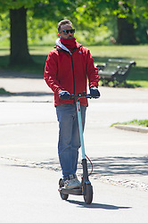 ©Licensed to London News Pictures 15/05/2020  <br /> Greenwich, UK. A man on an electric scooter. Warm sunny weather in Greenwich park, Greenwich, London as people get out of the house from coronavirus lockdown to exercise and enjoy more freedom to meet family and friends. Photo credit:Grant Falvey/LNP