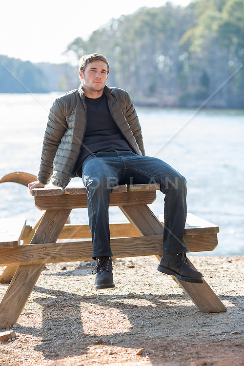 man relaxing on a picnic table by a lake