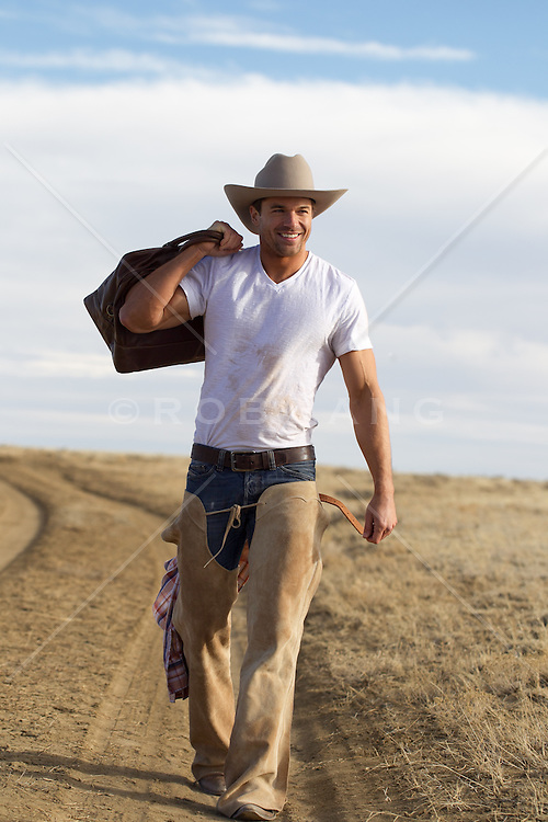 cowboy walking on a dirt road smiling