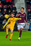 Keaghan Jacobs (#7) of Livingston FC clears the ball ahead of Sean Clare (#8) of Heart of Midlothian FC during the Ladbrokes Scottish Premiership match between Heart of Midlothian FC and Livingston FC at Tynecastle Park, Edinburgh, Scotland on 4 December 2019.