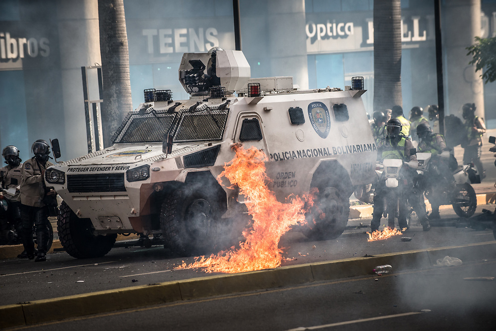 CARACAS, VENEZUELA - MAY 20, 2017:  Fire from an exploded molotov cocktail thrown by anti-government protesters burns next to a police tank. The streets of Caracas and other cities across Venezuela have been filled with tens of thousands of demonstrators for nearly 100 days of massive protests, held since April 1st. Protesters are enraged at the government for becoming an increasingly repressive, authoritarian regime that has delayed elections, used armed government loyalist to threaten dissidents, called for the Constitution to be re-written to favor them, jailed and tortured protesters and members of the political opposition, and whose corruption and failed economic policy has caused the current economic crisis that has led to widespread food and medicine shortages across the country.  Independent local media report nearly 100 people have been killed during protests and protest-related riots and looting.  The government currently only officially reports 75 deaths.  Over 2,000 people have been injured, and over 3,000 protesters have been detained by authorities.  PHOTO: Meridith Kohut