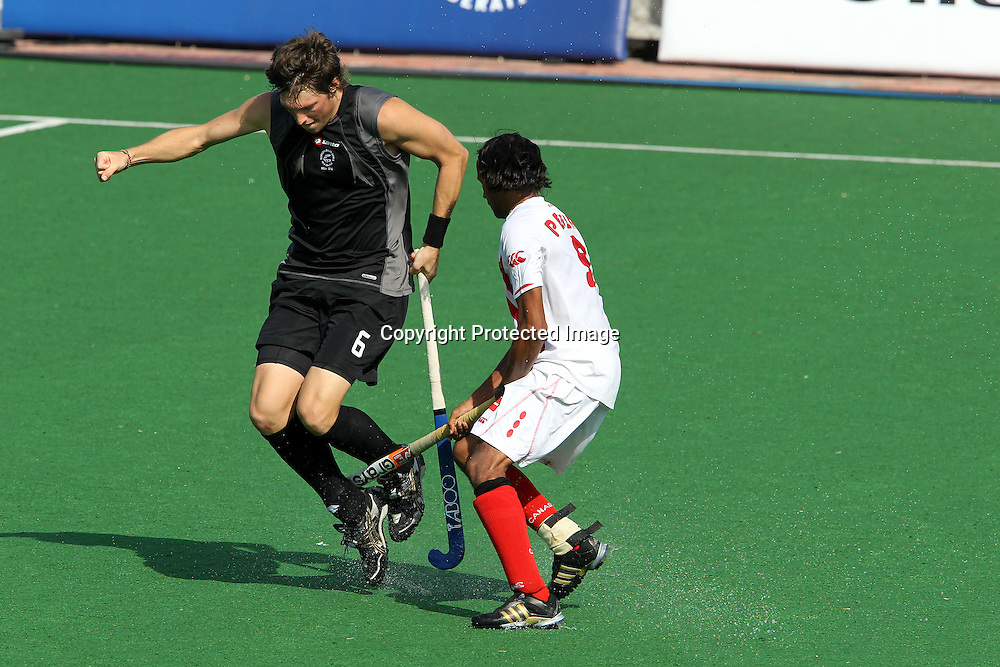 Simon Childs of New Zealand is fouled by Kenny Pereira of Canada during the hockey match between New Zealand and Canada during the XiX Commonwealth Games  held at the MDC Stadium in New Delhi, India on the  10 October 2010<br /> <br /> Photo by:  Ron Gaunt/photosport.co.nz