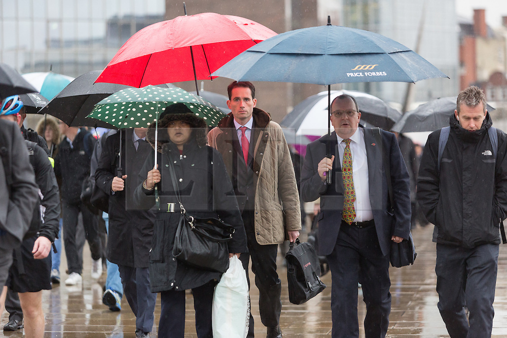 © Licensed to London News Pictures. 28/10/2015. London, UK. Commuters make their way to work across London Bridge during heavy rain and wet weather this morning. Photo credit : Vickie Flores/LNP