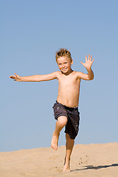 Boy running down sand dune against a blue sky