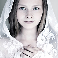 Female youth with sad expression wearing white lace veil looking at camera