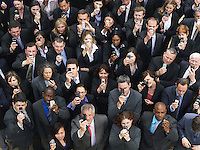 Large group of business people taking photographs with mobile phones elevated view