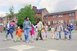 Single parents walking across primary school playground with children,