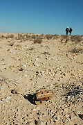 Israel, Negev plains, A group hiking on the mountain. Remains of an old mortar shell in the foreground