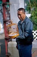 A man walks his bird in a cage at the Yuen Po Street Bird Garden in Kowloon, Hong Kong, China.