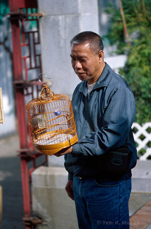 A man walks his bird in a cage at the Yuen Po Street Bird Garden in Kowloon, Hong Kong, China.