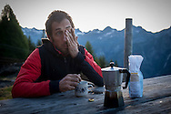 Beñat haves his first coffee early in the morning. Village of Brontallo (Switzerland)  July 03, 2014. Beñat and Nathalie spend two months (July and August) on Spulüi, at 1.900 meters, taking care of goats and making cheese. Their children Kemen (7 years old) and Oihu (18 months) are with them. (Gari Garaialde / Bostok Photo)
