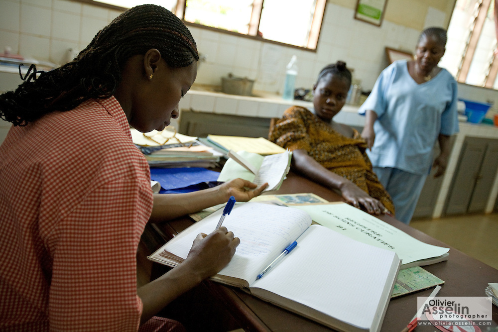 A health worker fills in a registry with medical information during a consultation with a pregnant woman at the Abomey health center in the town of Abomey, Benin on Monday September 17, 2007.