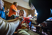 FLINT, MICHIGAN, USA - JANUARY 23: Grant Porter, 5, tries to look at a needle as his mother Ardis Porter, 26, tries to have him look away and comfort him while having his blood drawn to be tested for lead at Saturday, January 23, 2016 at the Masonic Temple in downtown Flint, Michigan. (Photo by Bryan Mitchell for The Guardian)