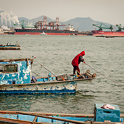 A woman works on her fishing boat near the site of an oil spill in Yeosu, South Korea.