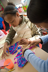 Two girls working on school project during art lesson,