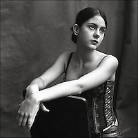 A young woman sitting relaxed on a chair wearing a basque