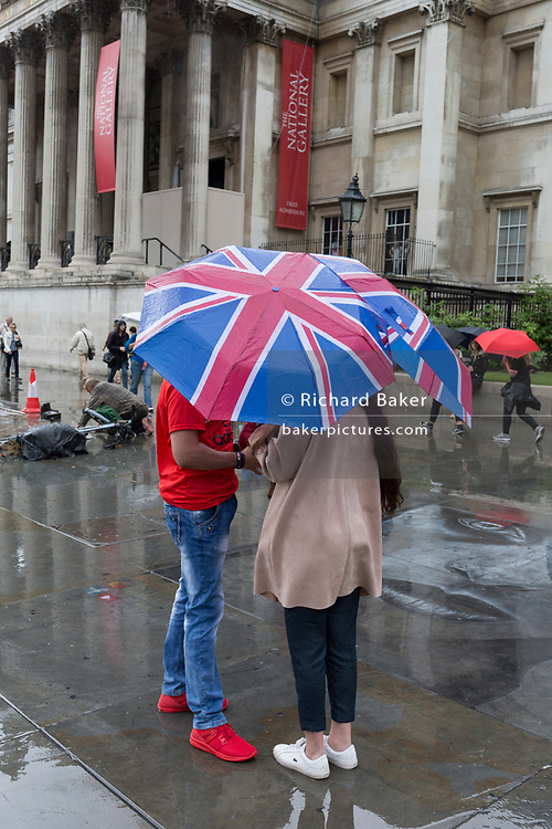 A couple shelters beneath a Union Jack umbrella during a sudden downpour in Trafalgar Square, on 13th August 2018, in London, England.