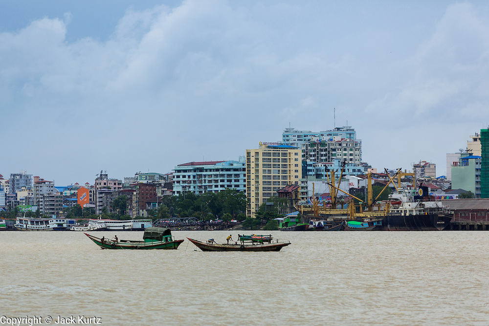 08 JUNE 2014 - YANGON, MYANMAR: The Yangon skyline as seen from the ferry to Dala in the Yangon River. The ferry to Dala runs continuously through the day between Yangon and Dala. Yangon, Myanmar (Rangoon, Burma). Yangon, with a population of over five million, continues to be the country's largest city and the most important commercial center.      PHOTO BY JACK KURTZ
