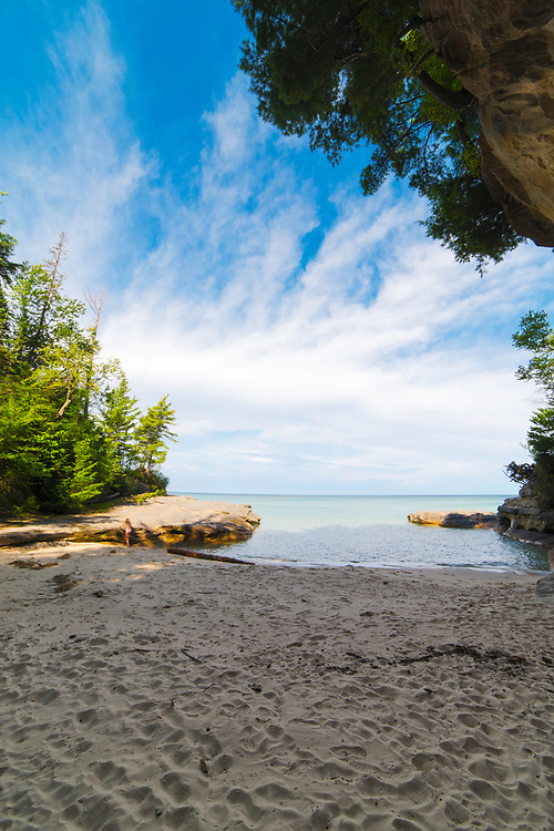 "A young girl walks in the sand. Image from the area known as ""The Cove,"" Pictured Rocks National Lakeshore, Michigan, USA."