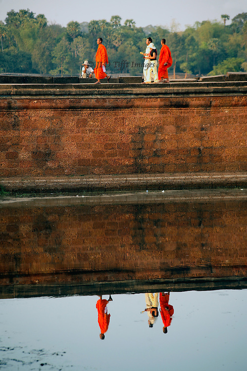 Angkor Wat: figures of people leaving the temple are reflected in the moat as they cross it.