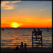Sea Cliff, NY: June, 2015--- People watch a beautiful Long Island sunset on Hempstead Harbor from Sea Cliff Beach.