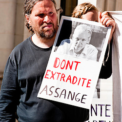 """LONDON, UK - 30th May 2012: a protester holds a sign reading """"Don't extradite Assange outside The Supreme Court in London, minutes after Assange's loss of his extradition appeal."""