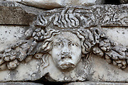 Mask and garland frieze from the Portico of Tiberius on the Southern portico of the Agora, 1st century AD, Aphrodisias, Aydin, Turkey. The Sculpture School at Aphrodisias was an important producer of carved marble sarcophagi and friezes from the 1st century BC until the 6th century AD. The Portico of Tiberius was built under the reign of Tiberius and has many examples of mask and garland friezes, consisting of the heads of gods, goddesses, theatrical characters, mythological figures or masks, each with a distinct facial expression, between hanging garlands of leaves, fruit and flowers. This example shows a sad face. Aphrodisias was a small ancient Greek city in Caria near the modern-day town of Geyre. It was named after Aphrodite, the Greek goddess of love, who had here her unique cult image, the Aphrodite of Aphrodisias. The city suffered major earthquakes in the 4th and 7th centuries which destroyed most of the ancient structures. Picture by Manuel Cohen