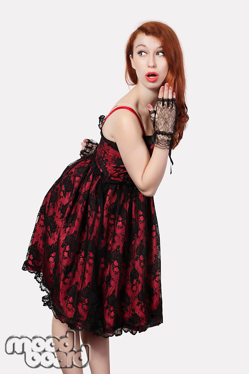 Shocked young woman in retro styled lace dress against gray background
