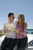 Young couple checking map at car