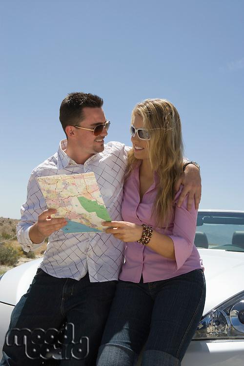 Young couple checking map at car