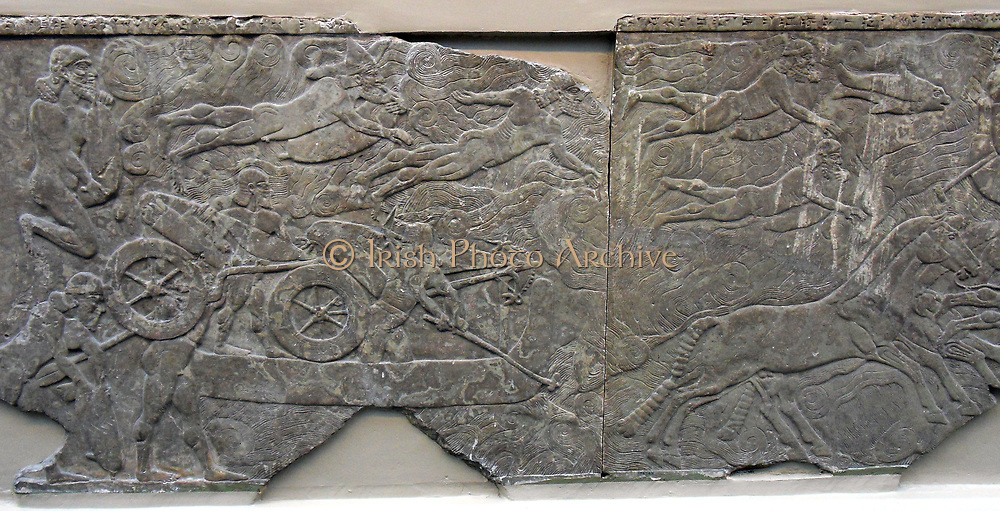 King Ashurnasirpal leads an attack on an enemy town. Soldiers cross the river by swimming. Assyrian relief 865-860 BC from Nimrud